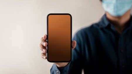 Mobile Phone Mockup Image. Display Screen is Blank. Person with a Surgical Mask on Face Holding a Smartphone towards the Camera. Front View Archivio Fotografico