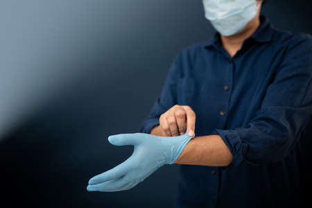 Person with Surgical Mask on Face try to Wearing a Medical Gloves. Keep Clean and Protection before do something. Lifestyle during Coronavirus Situation Archivio Fotografico