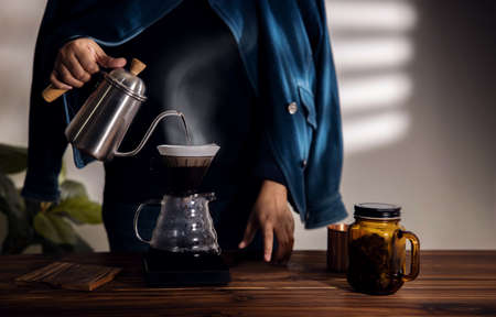 Person Dripping Coffee at Home in the Morning. Zen and Cozy Living. Pouring Hot Water from Kettle into a Dripper. Medium shot Archivio Fotografico