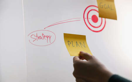 Goal, Plan, Challenge and Strategy Concept. Person making Business Plan on Sticky Note. Closeup and Selective Focus