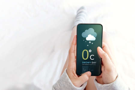 Snowy Day Concept. Cold Weather in Winter Season. Female Lying in Bed while Using Mobile Phone to see Weather Forecast on Screen. Top View