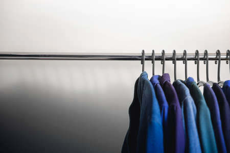 Wardrobe Rack. Men Clothes hanging on Bar by the White Wall. Fashion Lifestyle of a Stylish Man. Empty Space on left side 免版税图像