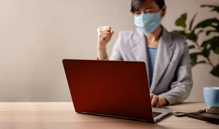 Small Business and Successful during Coronavirus Concept. blurred Gladful Business Woman wearing Mask, Working on Laptop in Office. Focus on Computer. Business Achieves Goals. Celebrating Success