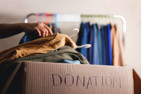 Donation Concept. Preparing Used Old Clothes from Wardrobe Rack into a Donate Box. Focus on Text Archivio Fotografico