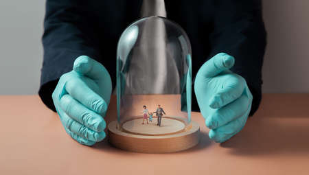 Safety and Health Insurance during Coronavirus Concept. Miniature Figure of Family walking inside a Glass Dome Cover. Hand with Medical Glove Protected them Archivio Fotografico