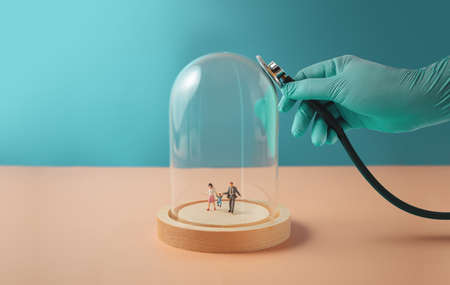 Health Care or Insurance during Coronavirus Concept. Hand of Doctor with Medical Glove Using a Medical Stethoscope to Check a Glass Dome. Miniature Figure of Family walking inside