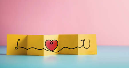 Love and Relationship Concept. Text and Heart Symbol on Fold Paper. Valentines Day Card. Message meaning as I Love You