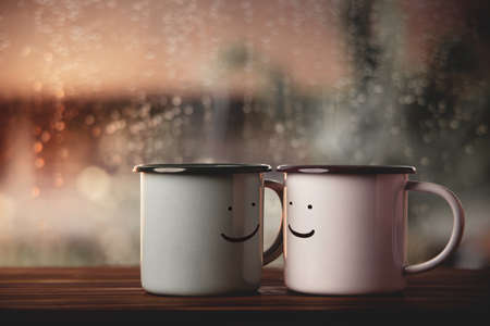 Love and Valentines Day Concept. Couple of Coffee Cup with Smiling face by Glass Window in House. Happiness, Romantic or Positive Mind on Rainy Day Foto de archivo