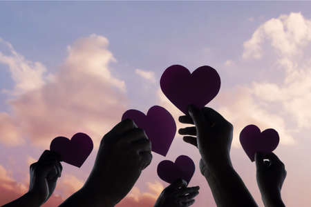 Love, Freedom and Charity Concept. Group of Diversity Volunteer People Raise Up Heart Paper Shape into the Sky