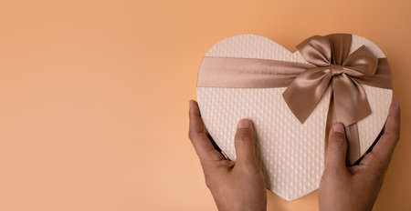 Love and Valentines Day Concept. Hands holding a Golden Heart Shape Gift Box. Top View