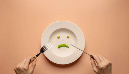 Diet or Anorexic in Health Care Concept. Eating Disorder. Lose Weight. Young Woman Using Fork and Knife to Eating Green Soy Bean on Plate.  Unhappy Food. Top View