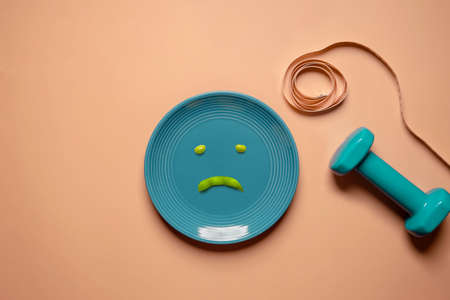 Diet and Health Care Concept. Try to Lose Weight. Green Soy Bean on Plate.  Unhappy Food. Surrounded by Dumbbell and Soft Tape Measure. Top View Foto de archivo