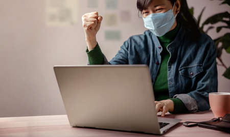 Small Business and Successful during  virus Concept. blurred Gladful Business Woman wearing Mask, Working on Computer Laptop in Office. Focus on Hand. Business Achieves Goals. Celebrating Success