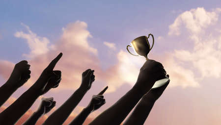 Teamwork, Winning, Goal and Successful Concept.  Silhouette of People Raise Up Hands into the Sky. the Leader Holding a Golden Trophy. Cheerful Gesture Hand
