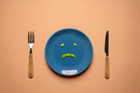 Diet or Anorexic in Health Care Concept. Eating Disorder. Try to Lose Weight. Green Soy Bean on Plate Surrounded by Fork and Knife.  Unhappy Food. Top View