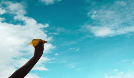 Goal, Challenge and Successful or Travel Concept. Person Raise Up a Paper Plane into the Sky, Dreaming or Planing for a Vacation. Low angle View. Metaphor photo Imagens