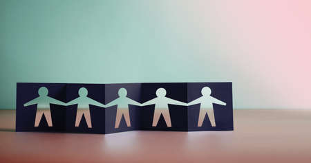Teamwork, Partnership, Humanity and Unity Concept. Human Sign Shape cut out on Fold Paper, Metaphor Photo. People Holding Hands Together