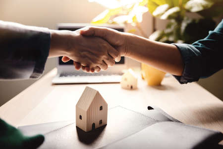 Buying a New House Concept. Real Estate Agent making Handshake with Customer. Submit Deals and Sale Contract