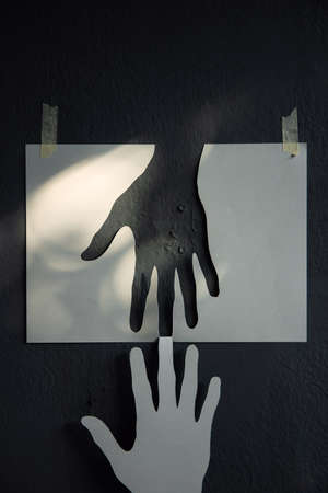Help, Care, Support or Partnership Concept. Paper Cut as Hands Shape hanging on the wall. look like the top one trying to help the one below. Touching each other Stock fotó