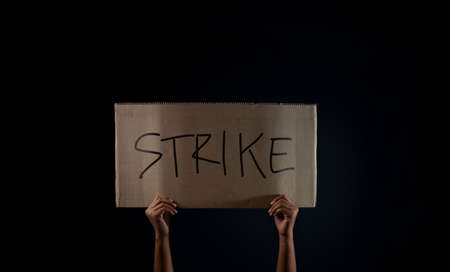 Protest , Strike, Mob or Expression Concept. Person Raised a Corrugated Paper with Text. Front View and Dark tone