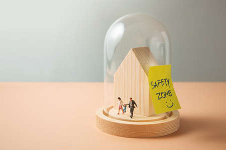 Safety Zone, Love and Care Concept. Miniature Figure of Family walking inside a Glass Dome Cover