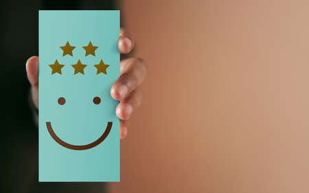 Customer Experience Concept. Happy Client giving Positive Review on Paper Card. Feedback a Happy Face Icon and Five Star Rating . Client's Satisfaction Surveys. Marketing Strategy Stock fotó