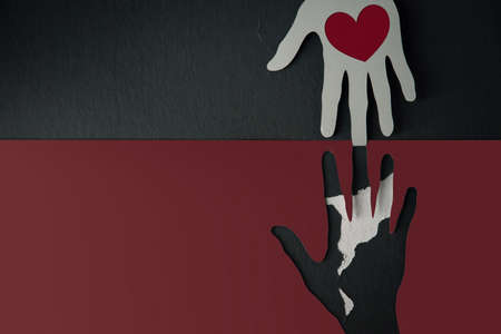 Donation Concept. Help, Care, Love, Support or Partnership. Paper Cut as Hands Shape hanging on the wall. look like the top one with a Red Heart trying to help the one below