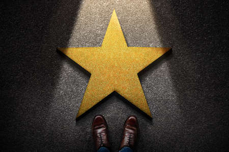 Success in Business or Personal Talent Concept. Top View of Business Person in Working Shoes Standing in front of a Golden Star. Light Shining on the Dark Cement Floor Stock fotó