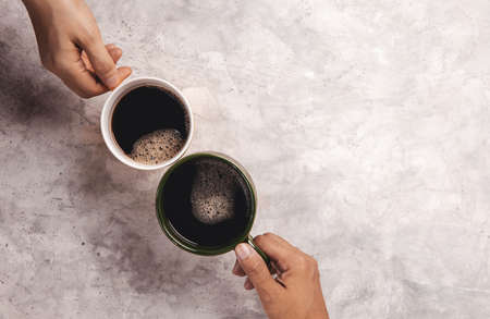 Moring Drink Concept. Couple or Two Friends holding a Cup of Coffee to making Cheers in Cafe or Restaurant . Top View on Table Imagens