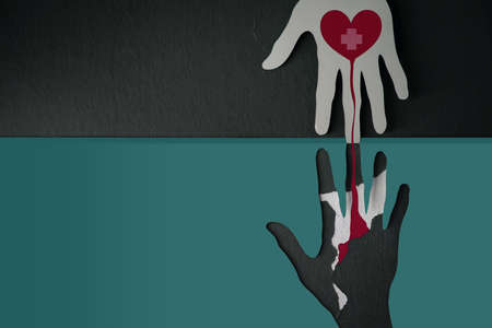 Blood Donation Concept. Help, Care, Love, Support. Paper Cut as Hand Shape hanging on the wall. look like the top one with a Red Heart and Cross Giving Blood to the one below