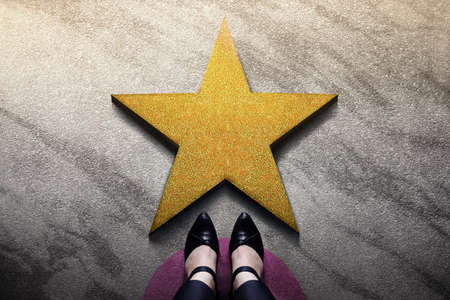 Success in Business or Personal Talent Concept. Top View of Business Woman in Working Shoes Standing in front of a Golden Star. Light Shining on the Dark Cement Floor