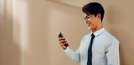 Portrait of a Smiling Young Asian Businessman Using Mobile Phone by the Wall