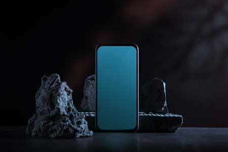 Mockup photo of Mobile Phone. Smartphone Screen as Clipping path. Dark Scene, surrounded by Concrete pieces