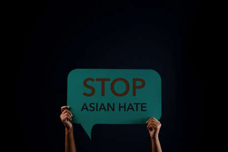 Stop Asian Hate Concept. Campaign, Protest or Expression Concept. Person Raised Up a Bubble Speech Paper with text in the Dark. Front View