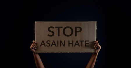 Stop Asian Hate Concept. Campaign, Protest or Expression Concept. Person Raised a Corrugated Paper with Text. Front View and Dark tone