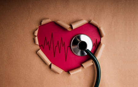 World Health Day. International World Heart Day Concept. Craft Paper as Heart Shape with Beat Rate and Stethoscope inside. Life, Love and Care. Top View Stock Photo