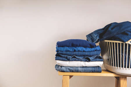 Clothes Concept. Stack of Clothing on Wooden bench by the Whaite Wall. Blue Navy Tone Stock Photo