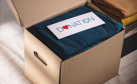 Clothes Donation Concept. Box of Cloth with Donate label. Preparing Used Old Garment at Home. Top View