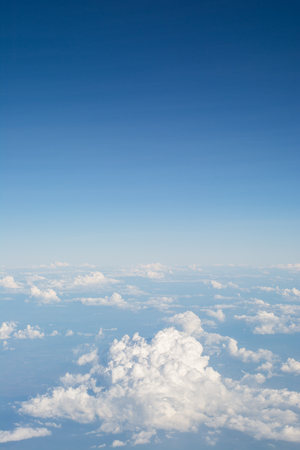 Clouds in blue sky, aerial view from airplane window.