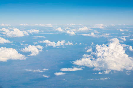 trip over: Clouds in blue sky, aerial view from airplane window.