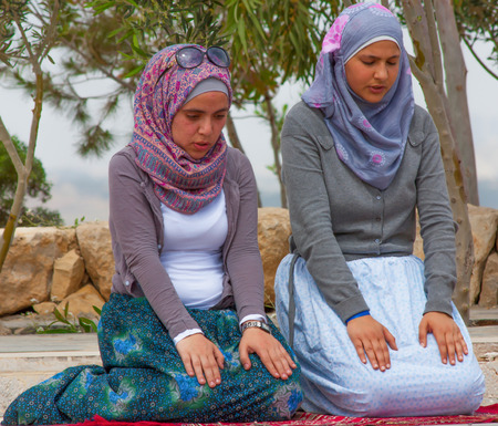 Amman, Jordan - the great majority of Jordan inhanitants is muslim. Here in the picture two young ladies praying