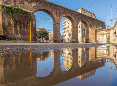 Rome, Italy - in Winter time, frequent rain showers create pools in which the wonderful Old Town of Rome reflect like in a mirror. Here in particular Piazza di Porta Maggiore