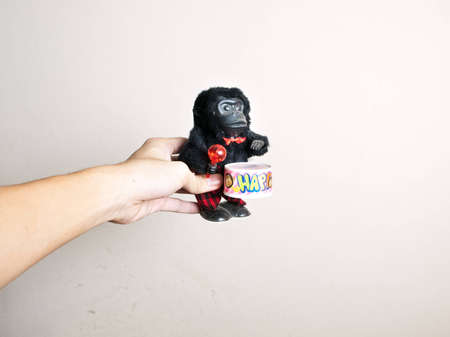 funny black monkey on drum toy in hand on white background