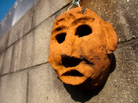 orange human face biscuit-fired ceramic art hanging on the wall  Stock Photo