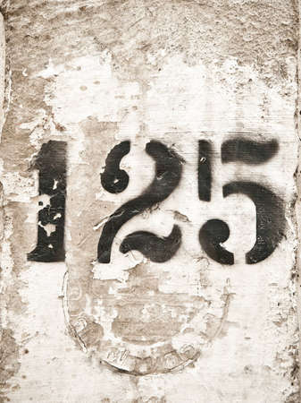 Old concrete pole stencil sign with the number 125