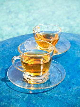 clear glass cup of tea on blue rock table