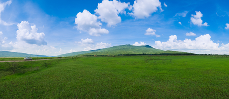 Green grass Field Meadow, White Cloud, Blue Sky with Mountain of Khao Yai Thiang in Amphoe Sikhio, Nakhon Ratchasima, Thailand.