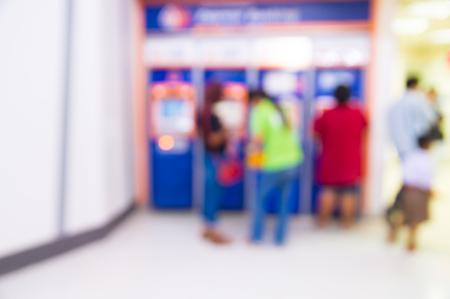 Abstract Blur Background or Defocus of People line up as Queue to make Transaction at ATM or Automatic Teller Machine in front of Bank Branch as Electronic Banking Concept 免版税图像