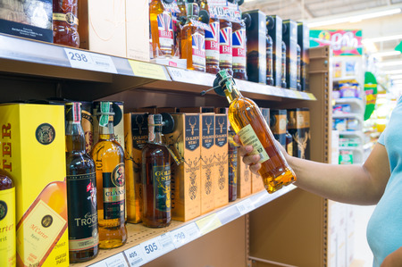 Nakhon Ratchasima, Thailand – June 20, 2017 : Unidentified Woman Picking Bottle of Alcohol Beverage from Shelf in Supermarket.  Thailand is one of Big Market of Liquor products in the world. 新闻类图片