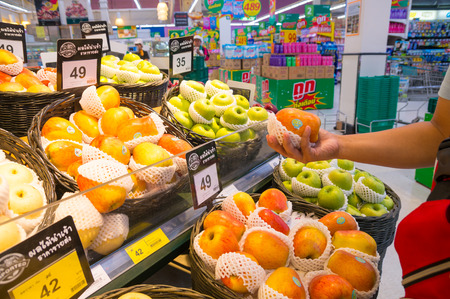 Nakhon Ratchasima, Thailand – June 20, 2017 : Red Fresh Apple in Hand of Unidentified Asian Woman while Select Fruit in Supermarket or Shopping Mall in Thailand. 免版税图像 - 81252452